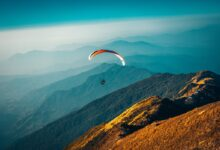 someone paragliding over mountains