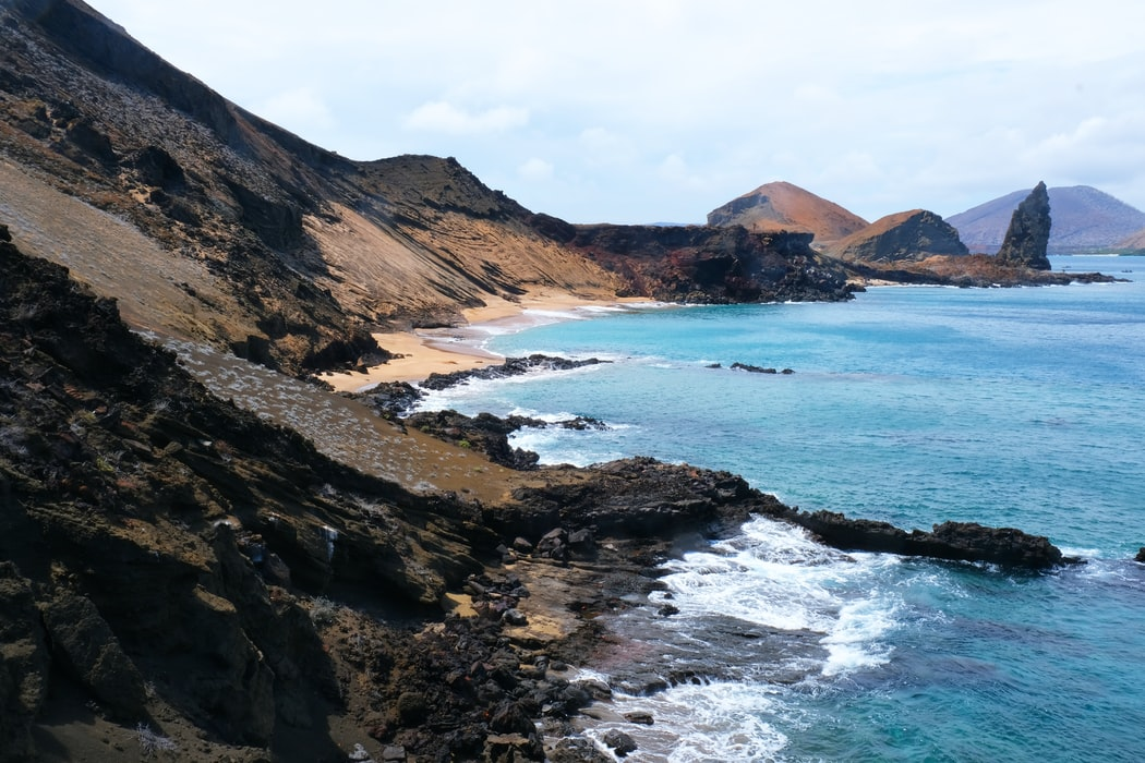 the shore of an island with black volcanic rock and blue water