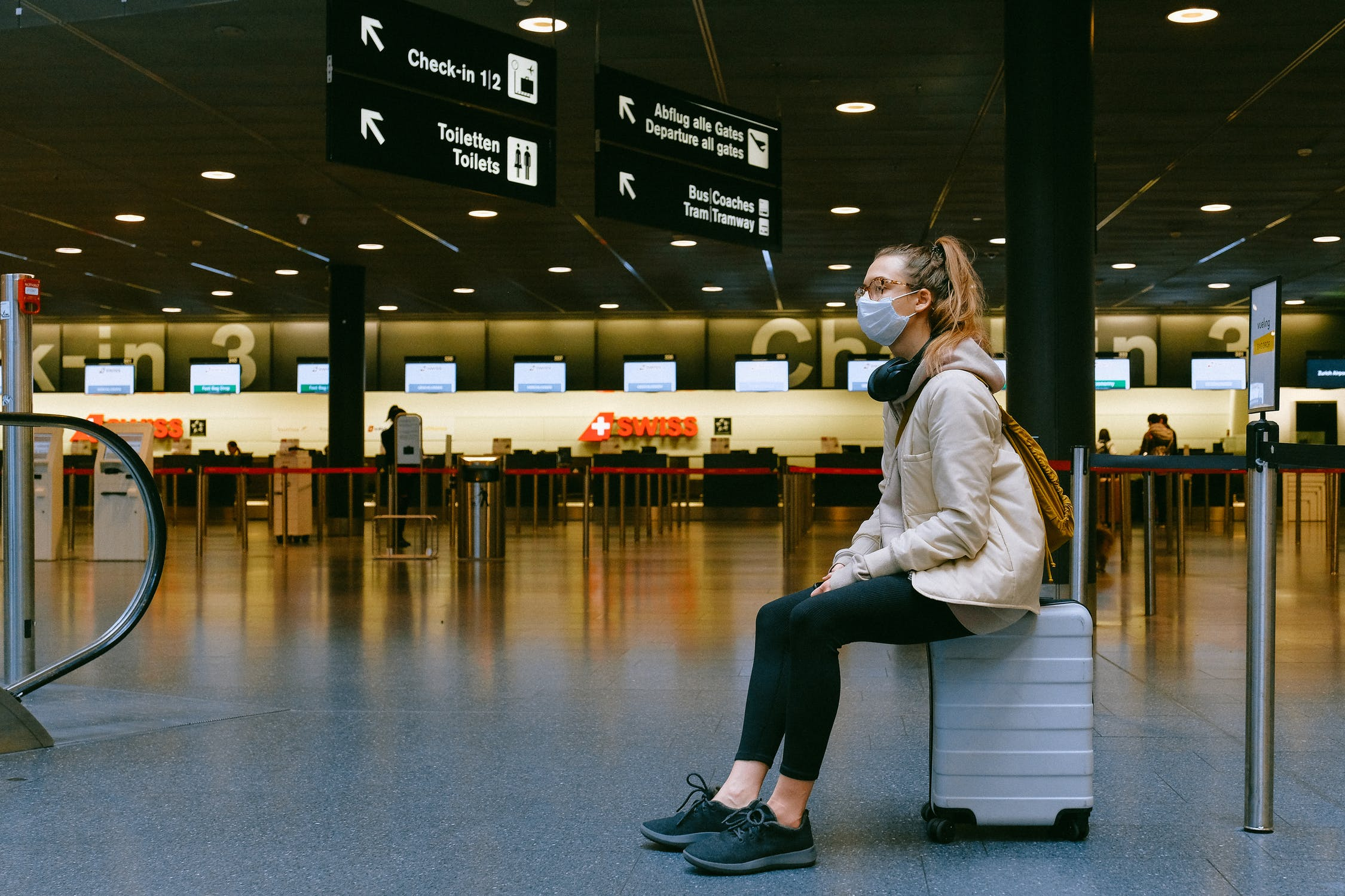person wearing a mask sitting on a suitcase in an airport