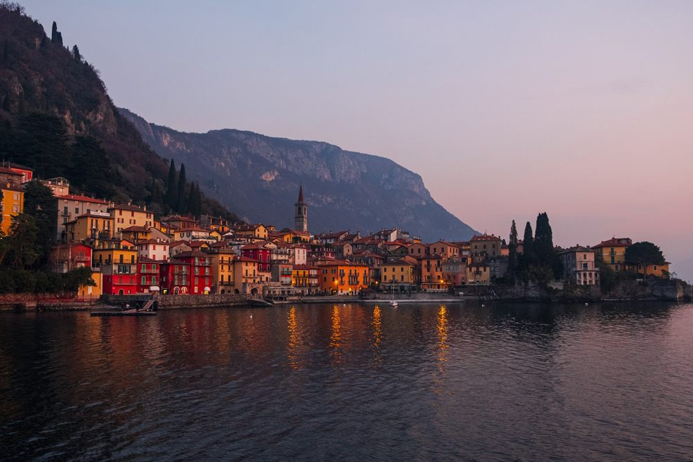 Sunset view of a lit up town along a lake