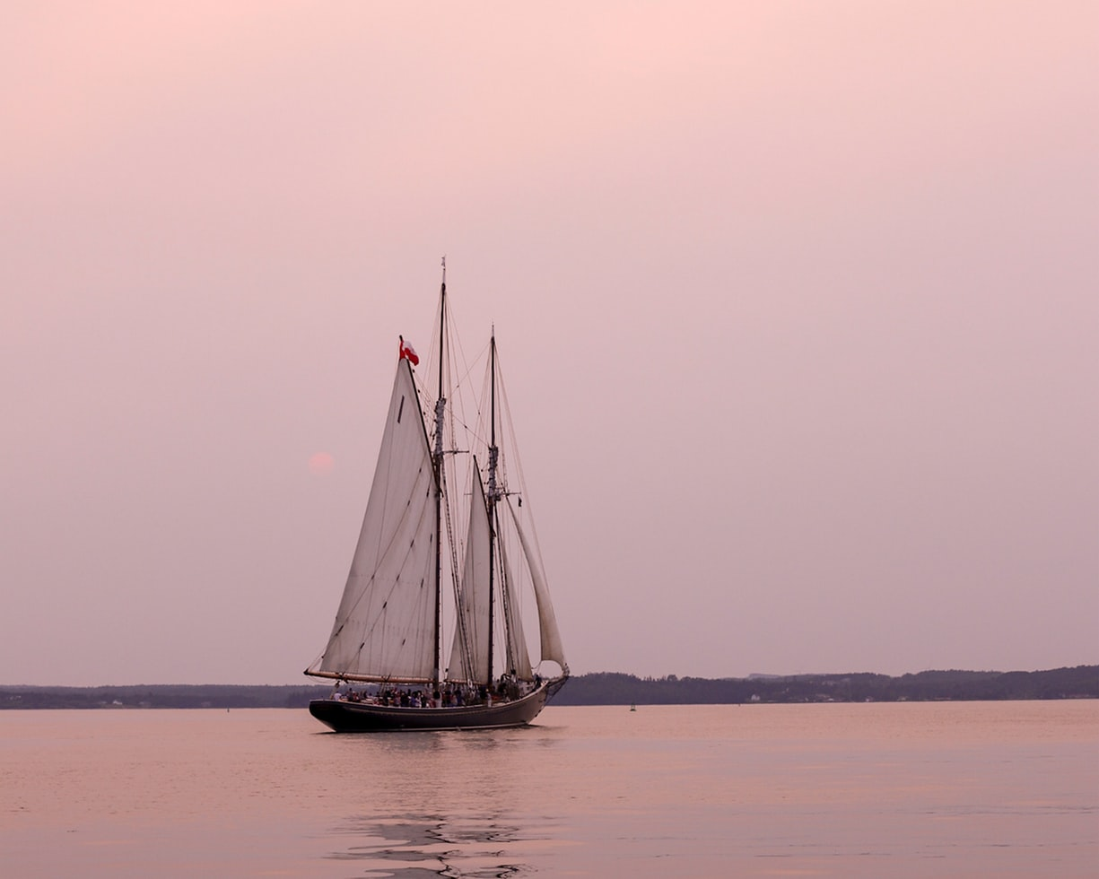 A boat with big sails sailing a sunset