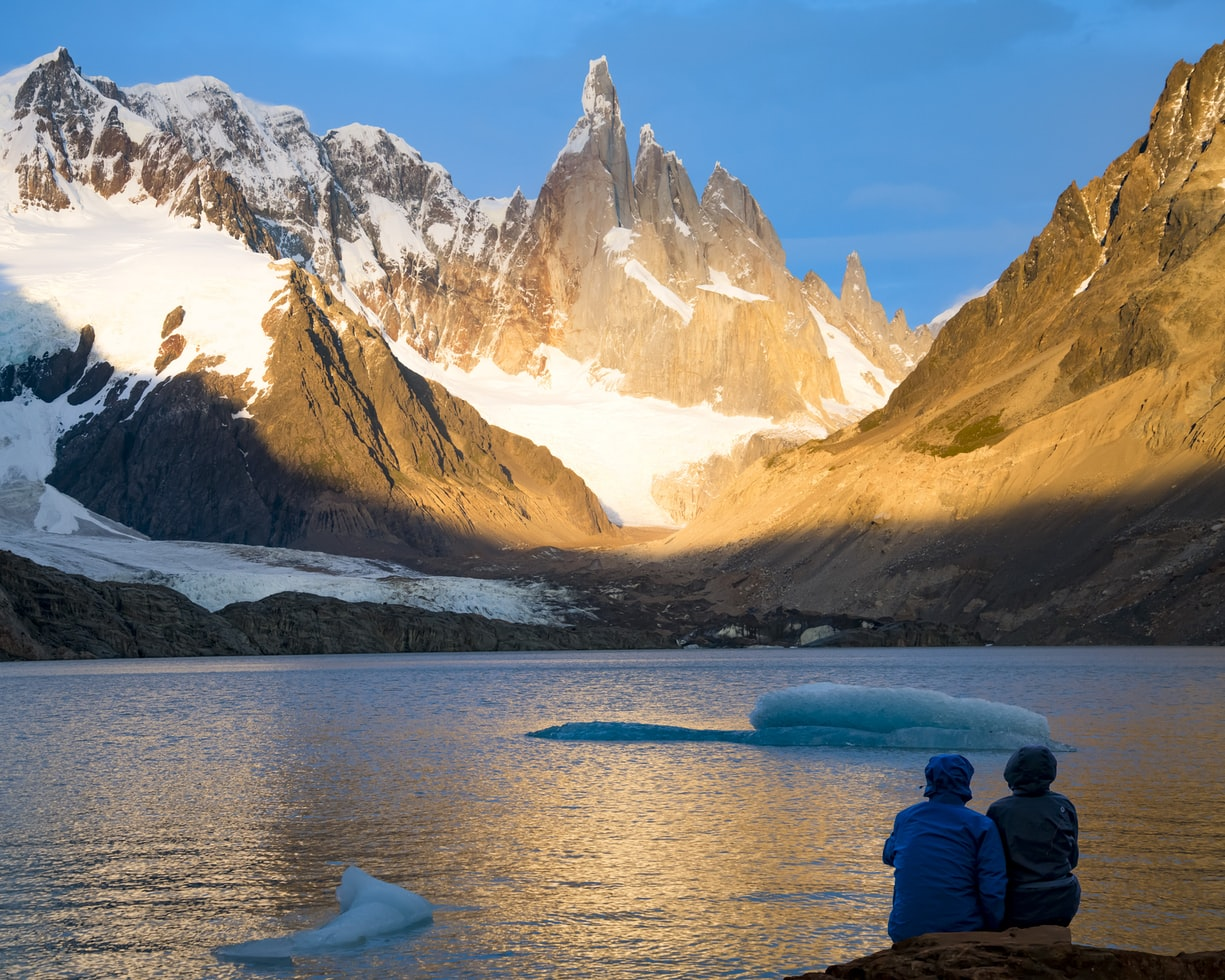 Two people sitting lakeside surrounded by mountains