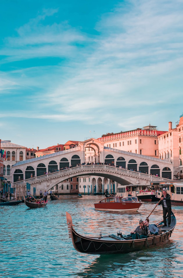 Gondola floating along a canal in front of Rialto bridge in Venice