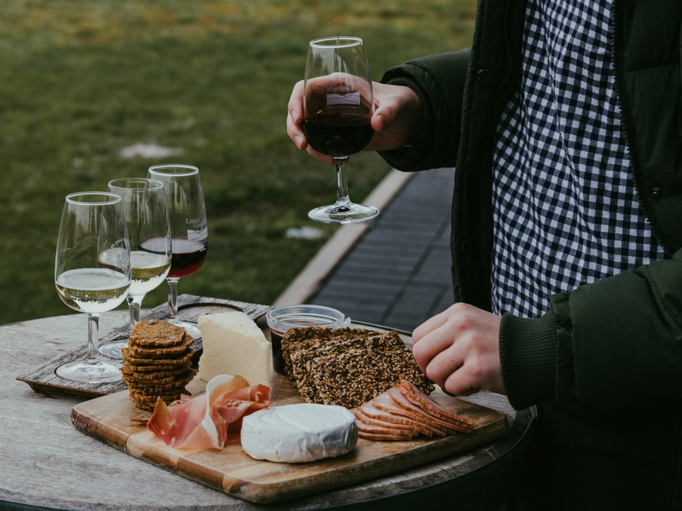 Someone enjoying wine and a charcuterie board