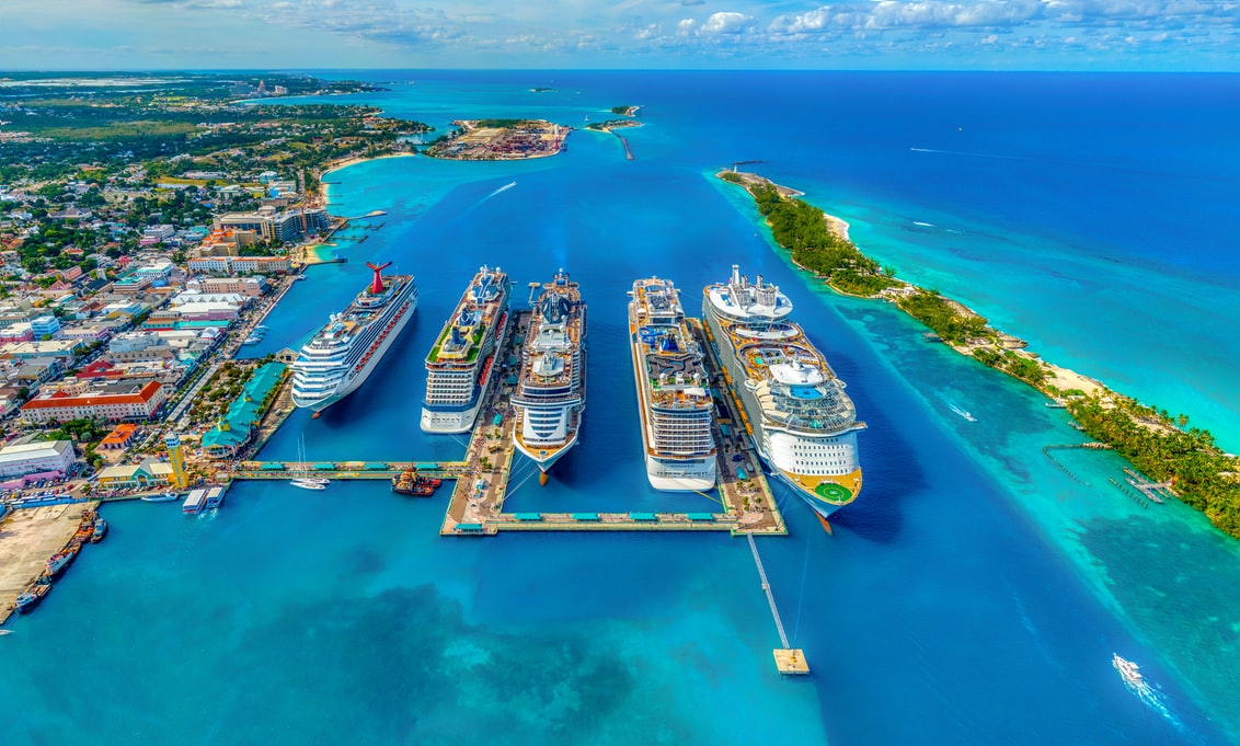 five cruise ships sitting a port on a blue ocean