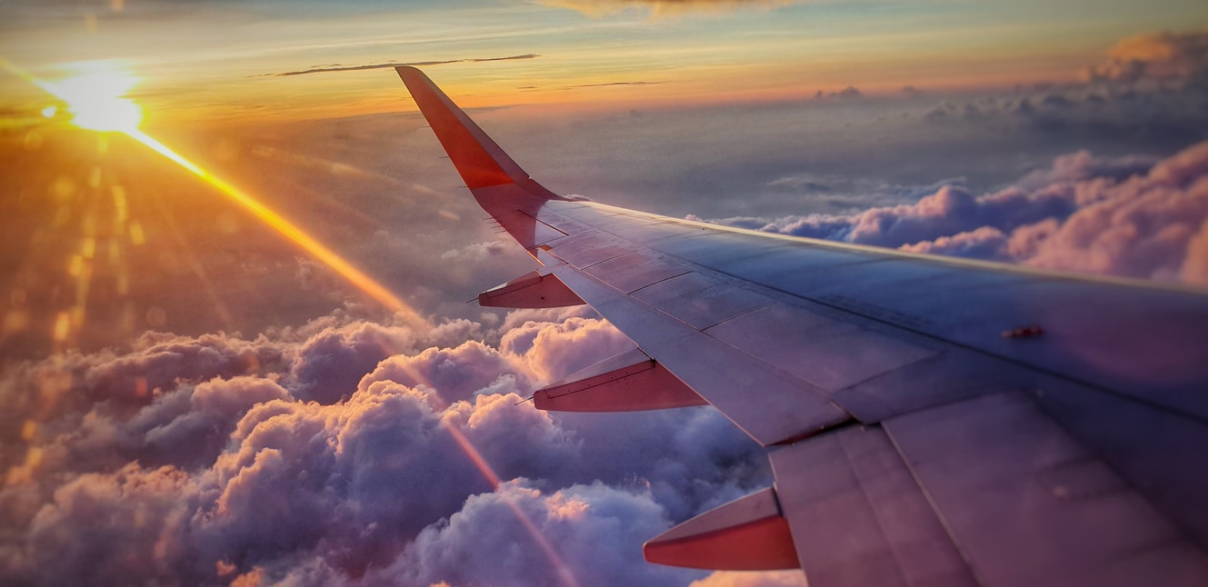 Airplane wing flying in a cloudy sky at sunset