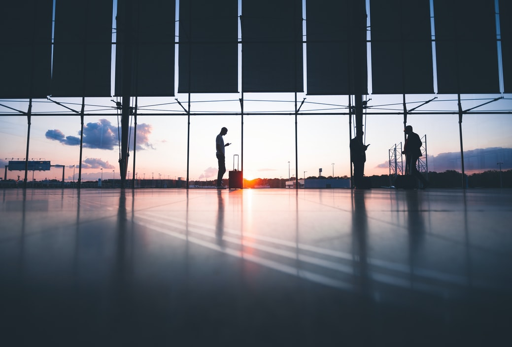 people silhouetted along floor to ceiling windows at sunset