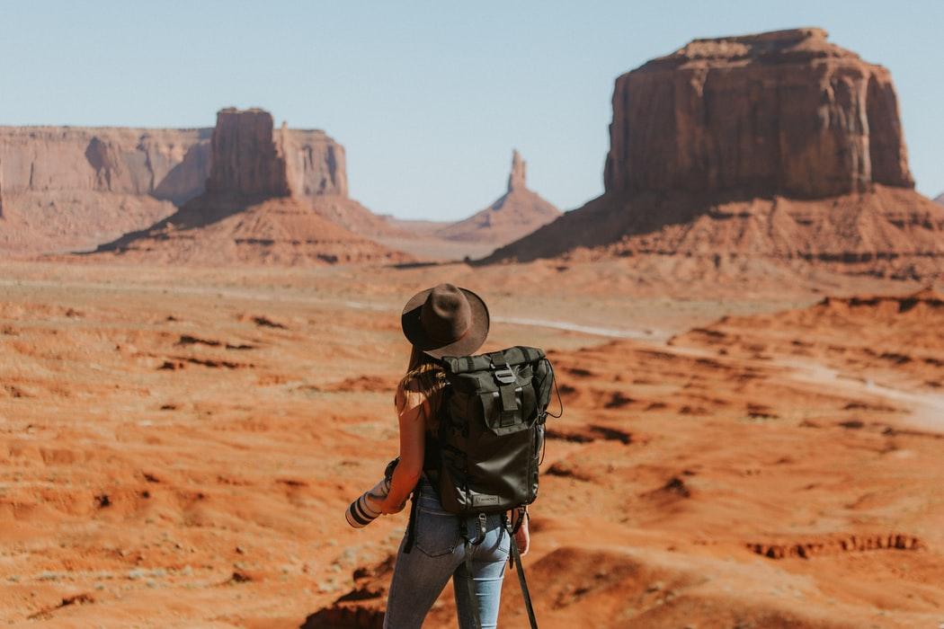 Traveler wearing a backpack in a desert