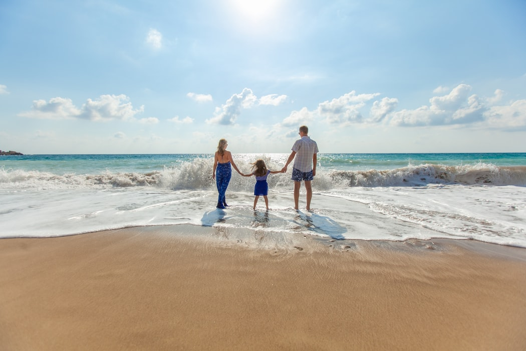 family standing on a beach by the ocean