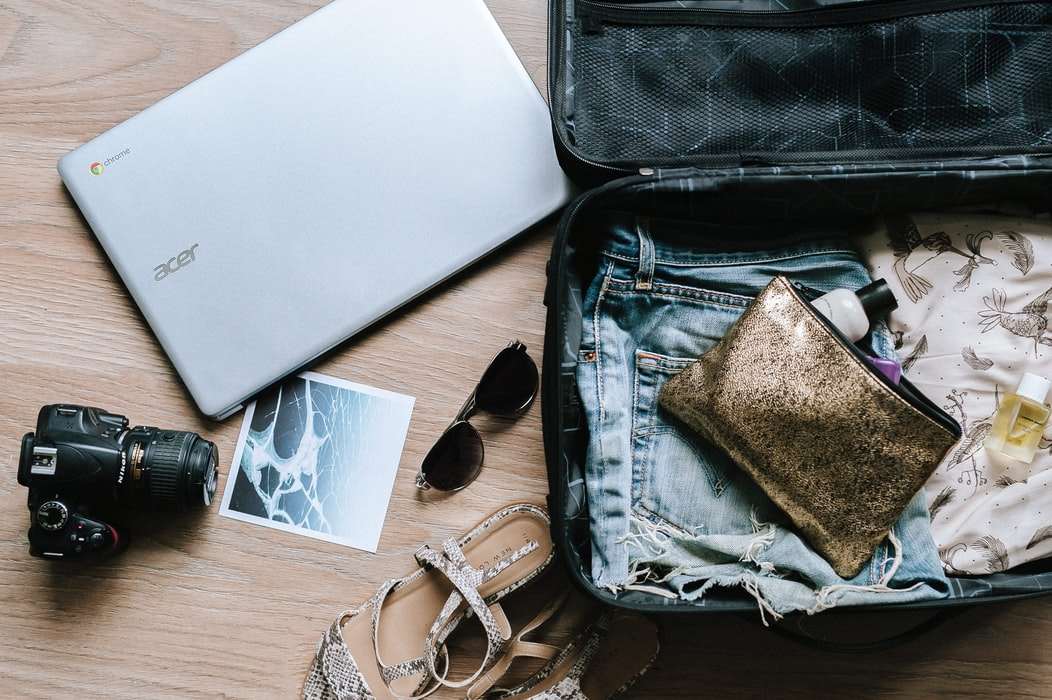 overhead view of a packed suitcase, a laptop and a camera