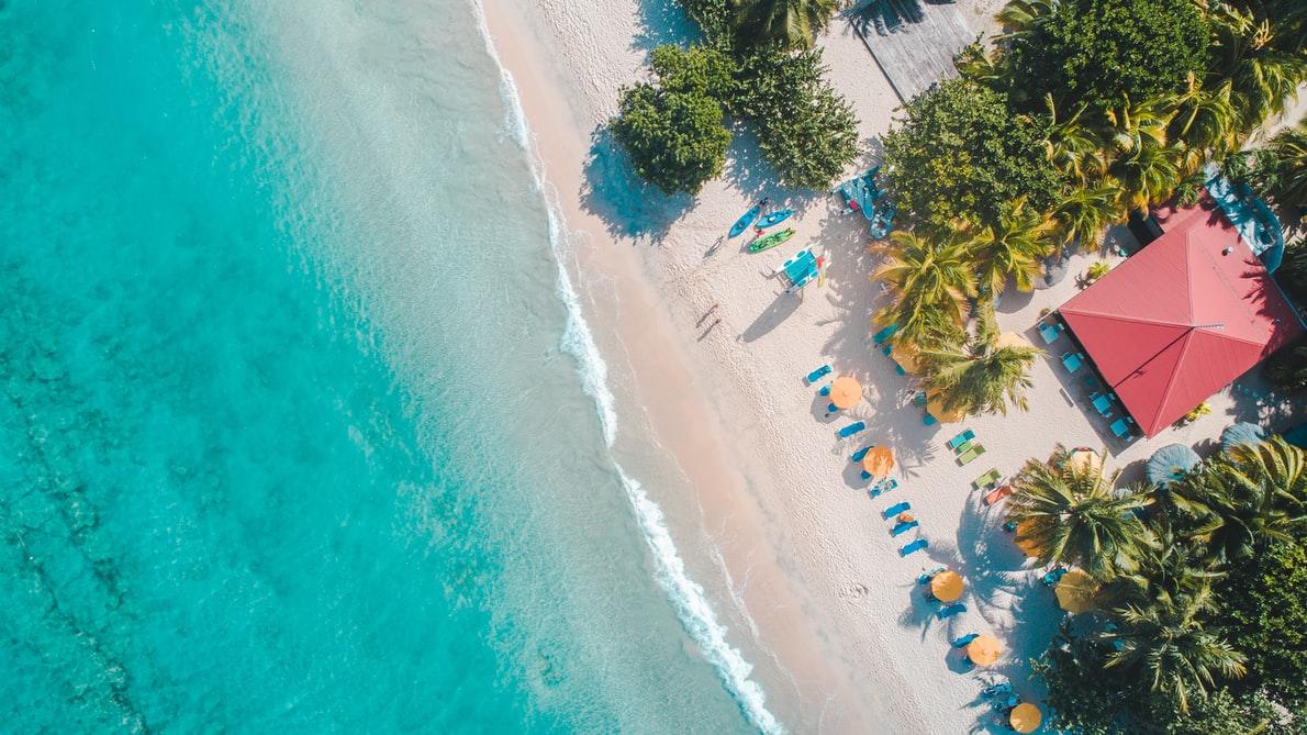 overhead view of a sandy beach and a blue ocean