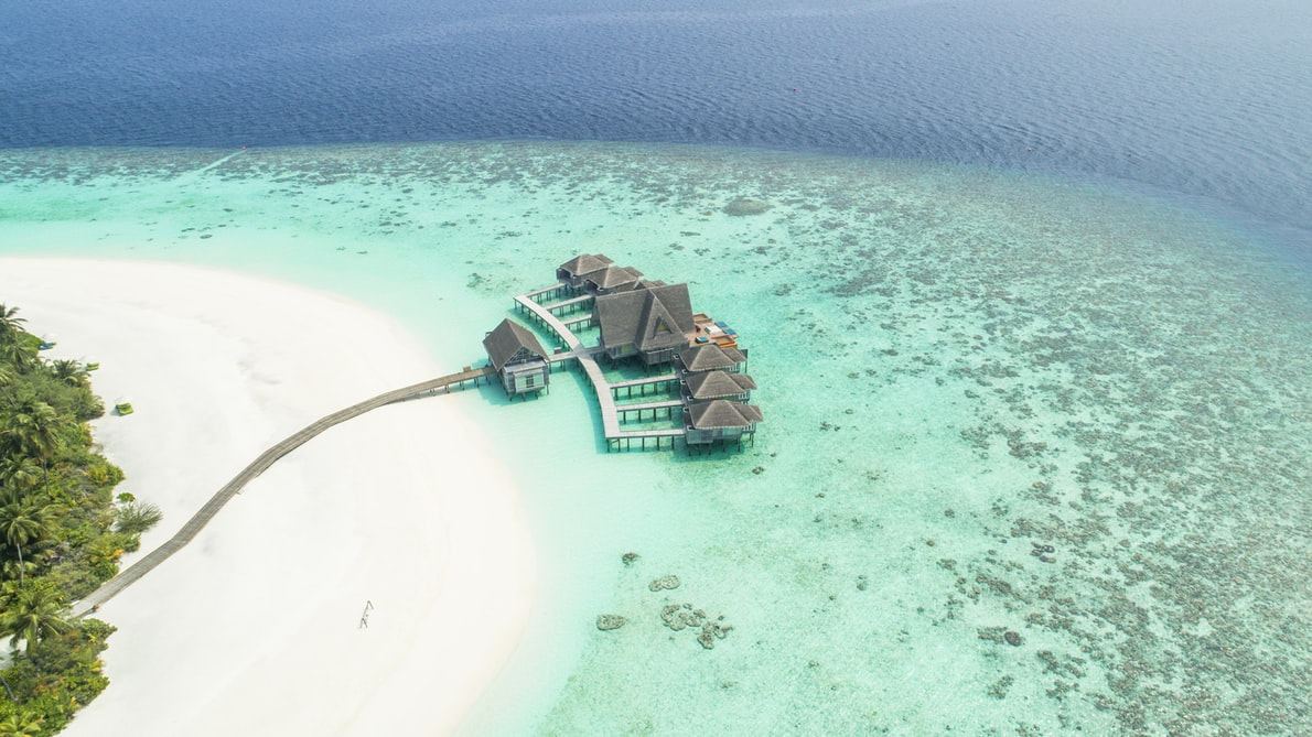 Overwater Bungalows in the ocean next to a beach