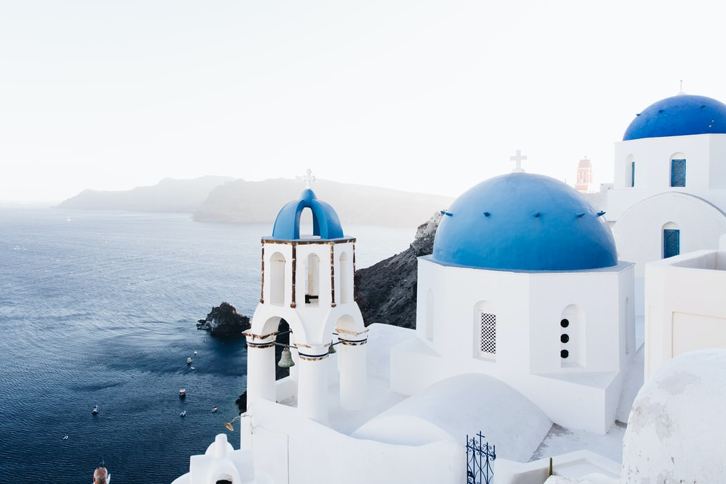 White buildings with blue roofs overlooking the ocean