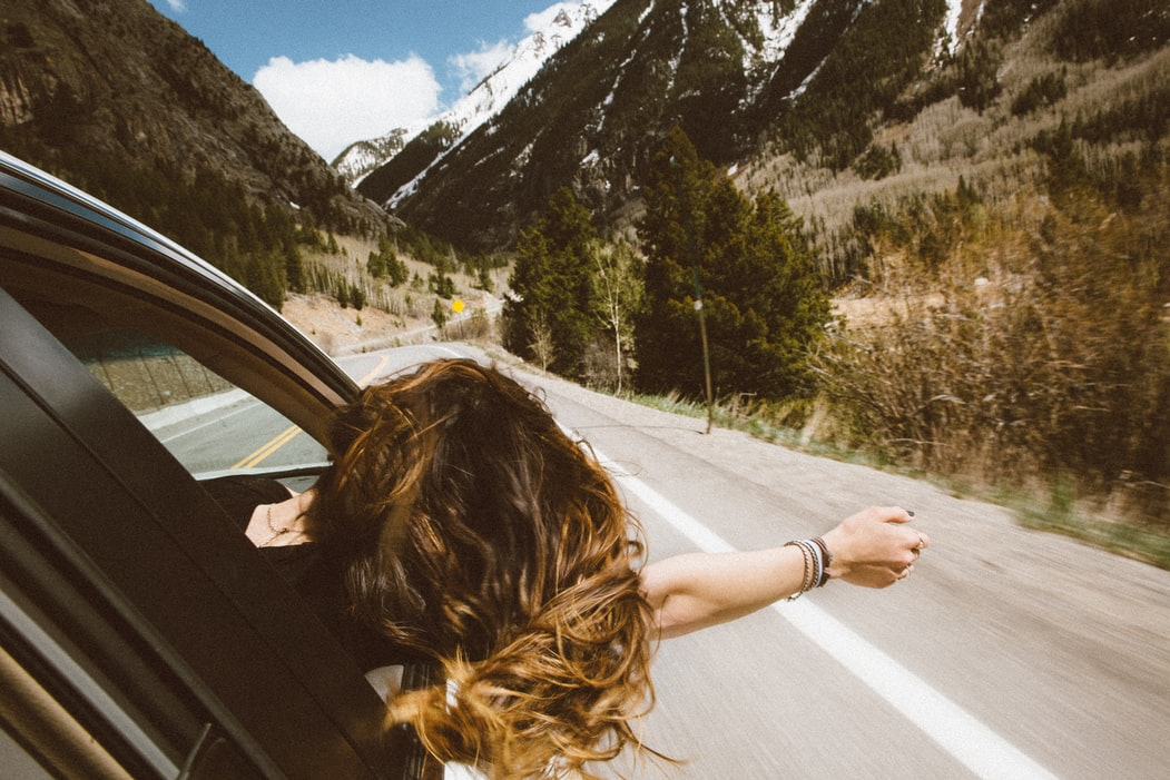 Person sticking their head out of a car window down a mountain road