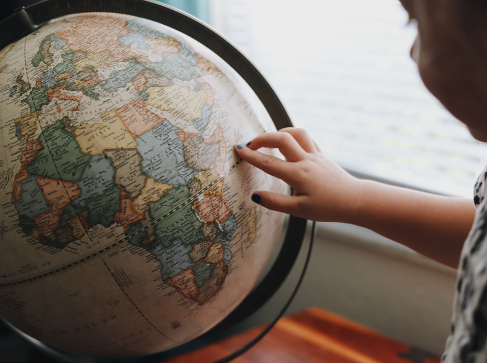 Person pointing at a globe